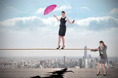 Young business woman pulling a tightrope for businesswoman Royalty Free Stock Photo