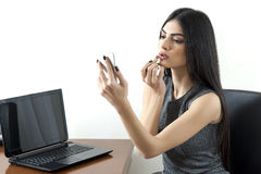 Young business woman putting lipstick before a meeting. royalty free stock image