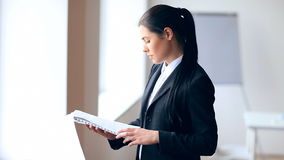 Young business woman reading documents in office stock video footage