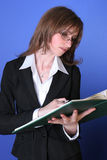 Young business woman reading a green file. Image of a business women reading concentrated a green file with a pen in her hand,suggesting attention and Stock Photos