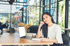 Young business woman reading a report her hand holding a pen sitting in a coffee shop stock photography