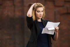 Young business woman reading a tax letter in city street Royalty Free Stock Photography
