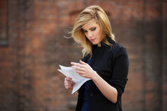 Young business woman reading a tax letter in city street Royalty Free Stock Photo