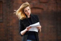 Young business woman reading a tax letter on city street Stock Photography