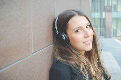Young business woman relaxes listening to music in the city Stock Images