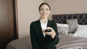 Young business woman relaxing in hotel room and looking tv, choose chanel with remote control. Young business woman relaxing in hotel room and looking tv stock video