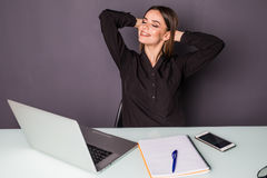 The young business woman is relaxing at work with hands over head. The young business woman is relaxing at work Stock Images