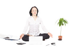 Young business woman resting in lotus pose in front of laptop on stock photo