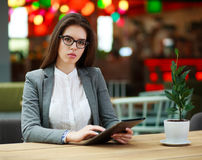 Young business woman in room with tablet computer at table Stock Photo