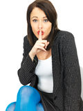 Young Business Woman with a Secret. A DSLR royalty free image, of a young business woman, being secretive holding a finger to her lips, while looking at camera Stock Image