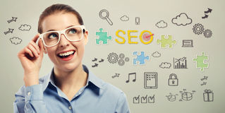 Young business woman with SEO concepts. Young business woman wearing big white eye glasses with SEO concepts Stock Photos