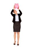 Young business woman shaking a piggybank Stock Photography