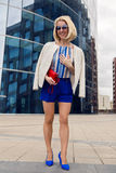 Young business woman in short blue trunks. Standing and waiting for a meetingfrom the Bank of glass , high building Stock Photos