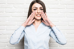 Young business woman shouting on brick wall Royalty Free Stock Image