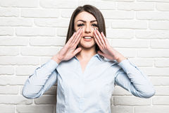 Young business woman shouting on brick wall Royalty Free Stock Photos