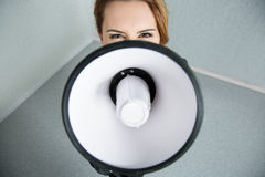 Young business woman shouting with a megaphone Royalty Free Stock Images