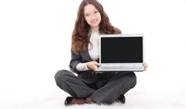 Young business woman showing a laptop sitting on the floor. Isolated on white royalty free stock image