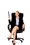 Young business woman sitting on armchair and pointing up with big pen Royalty Free Stock Images