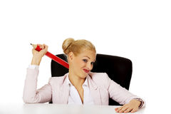 Young business woman sitting behind the desk and holding big pen Royalty Free Stock Photos
