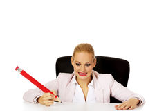 Young business woman sitting behind the desk and holding big pen Royalty Free Stock Images