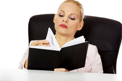 Young business woman sitting behind the desk and reading notes Royalty Free Stock Images