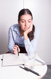 Young business woman is sitting bored in the office Stock Photo