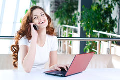 A young business woman sitting in a cafe. A young attractive business woman sitting in a cafe with a laptop and cell phone Royalty Free Stock Image