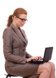 Young business woman sitting on chair with laptop. Beautiful young business woman sitting on a chair and working Royalty Free Stock Photos