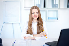 Young business woman sitting at desk Royalty Free Stock Photo