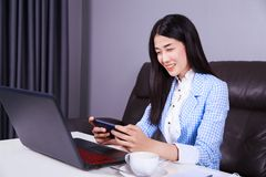 Business woman sitting at the desk with laptop and using mobile. Young business woman sitting at the desk with laptop and using mobile phone Royalty Free Stock Photo