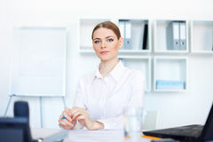 Young business woman sitting at desk in office Royalty Free Stock Photo