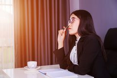 Business woman sitting at the desk and thinking to her work Royalty Free Stock Photography