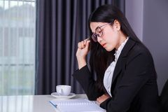 Business woman sitting at the desk and and thinking to her work Stock Photos