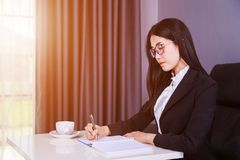 Business woman sitting at the desk and writes a note on the note Royalty Free Stock Photo