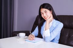 Business woman sitting at the desk and writes a note on the note Royalty Free Stock Photography
