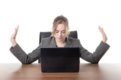 Young business woman sitting a her desk. Business woman sitting a a desk with a laptop computer in front of her Royalty Free Stock Photography