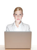 Young business woman sitting with laptop. Young business woman sitting at a table with laptop, looking at the camera Royalty Free Stock Image