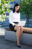 Young business woman sitting with laptop in city park Royalty Free Stock Image