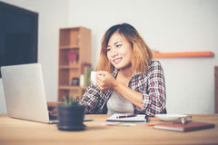Young business woman sitting in office desk with cup of coffee r Stock Photo