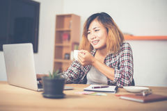 Young business woman sitting in office desk with cup of coffee r Stock Photos