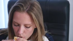 Young business woman sitting in the office and eating a burger stock video footage