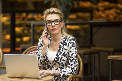Young business woman sitting in outdoors cafe with laptop talking on the phone. Royalty Free Stock Photography