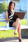 Young business woman sitting on a park bench Royalty Free Stock Photos