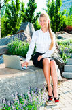 Young business woman. Sitting on a rock and using a laptop outdoors Stock Photos