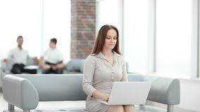 Young business woman sitting at sofa and working with laptop. At the waiting hall of the business center stock image