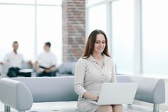 Young business woman sitting at sofa and working with laptop. At the waiting hall of the business center stock photo