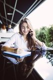 Young business woman sitting at table in cafe, talking oncell phone while taking notes in notebook on table laptop. Student learni. Young business woman in gray royalty free stock photo