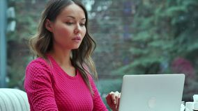Young business woman sitting at table and taking notes in notebook stock video footage