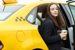 Young business woman sitting in taxi and holding coffee Royalty Free Stock Image