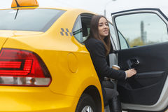Young business woman sitting in taxi and holding coffee Royalty Free Stock Images
